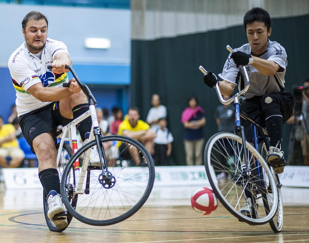 HONG KONG - AUGUST 17: Roman Schneider (L) of Switzerland and Yosuke Fujita of Japan fight for the ball during the UCI Cycle-Ball World Cup on August 17, 2013 at the Chai Wan Sports Centre in Hong Kong, China. (Photo by Victor Fraile/Getty Images)