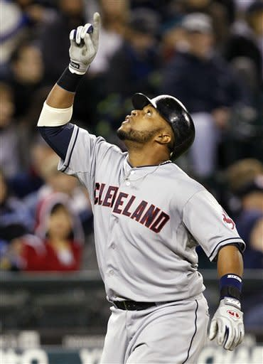 Cleveland Indians' Carlos Santana points skyward as he heads home on a three-run home run against the Seattle Mariners in the fifth inning of a baseball game Tuesday, April 17, 2012, in Seattle. (AP Photo/Elaine Thompson)