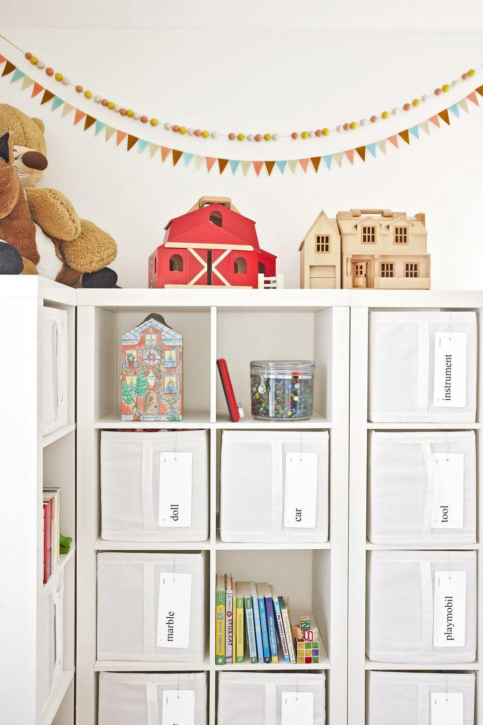 """<p>In this playroom, plain canvas toy bins get a cute and practical upgrade with hanging <a href=""""https://go.redirectingat.com?id=74968X1596630&url=https%3A%2F%2Fwww.etsy.com%2Fshop%2Fhaystackmercantile&sref=https%3A%2F%2Fwww.redbookmag.com%2Fhome%2Fg36014277%2Ftoy-organizer-ideas%2F"""" rel=""""nofollow noopener"""" target=""""_blank"""" data-ylk=""""slk:flashcard labels"""" class=""""link rapid-noclick-resp"""">flashcard labels</a> (marked """"marble,"""" """"doll,"""" """"train,"""" """"army,"""" and so forth).<br></p><p><sup><a class=""""link rapid-noclick-resp"""" href=""""https://www.amazon.com/AmazonBasics-Foldable-Storage-Cubes-6-Pack/dp/B0711RQMNF/ref=sr_1_6?tag=syn-yahoo-20&ascsubtag=%5Bartid%7C10063.g.36014277%5Bsrc%7Cyahoo-us"""" rel=""""nofollow noopener"""" target=""""_blank"""" data-ylk=""""slk:SHOP CANVAS BINS"""">SHOP CANVAS BINS</a></sup><br></p>"""