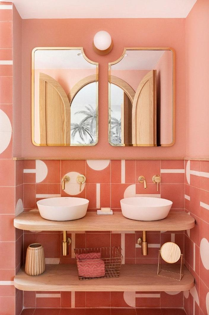 In the pink bathroom, the lighting is by Nuura, the sinks are by Bathco, the tiles are bespoke, and the mirrors were designed by Noé Prades Studio.