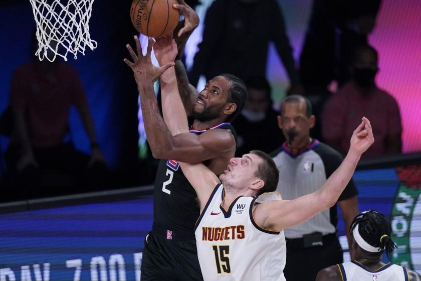 Los Angeles Clippers forward Kawhi Leonard (2) grabs a rebound over Denver Nuggets center Nikola Jokic (15) during the first half of an NBA conference semifinal playoff basketball game Tuesday, Sept. 15, 2020, in Lake Buena Vista, Fla. (AP Photo/Mark J. Terrill)