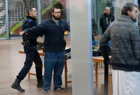 """Bilal El Makhoukhi (2nd L) and Michael Delefortrie (R), who are suspected of being part of """"Sharia4Belgium"""", pass the security check as they arrive for the verdict in the trial of the group in Antwerp February 11, 2015. REUTERS/Francois Lenoir"""