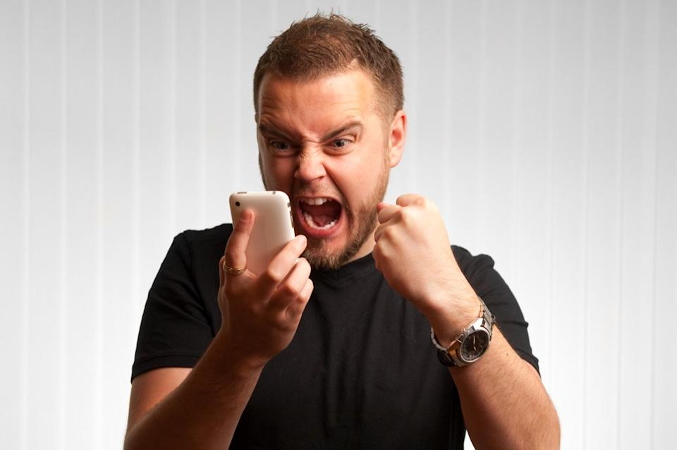 Angry man screaming into the phone and cursing during a bad conversation