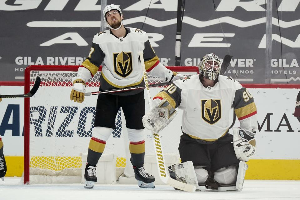 Vegas Golden Knights goaltender Robin Lehner (90) and defenseman Shea Theodore, left, pause on the ice after a goal was scored by Arizona Coyotes' Nick Schmaltz during the second period of an NHL hockey game Friday, Jan. 22, 2021, in Glendale, Ariz. (AP Photo/Ross D. Franklin)
