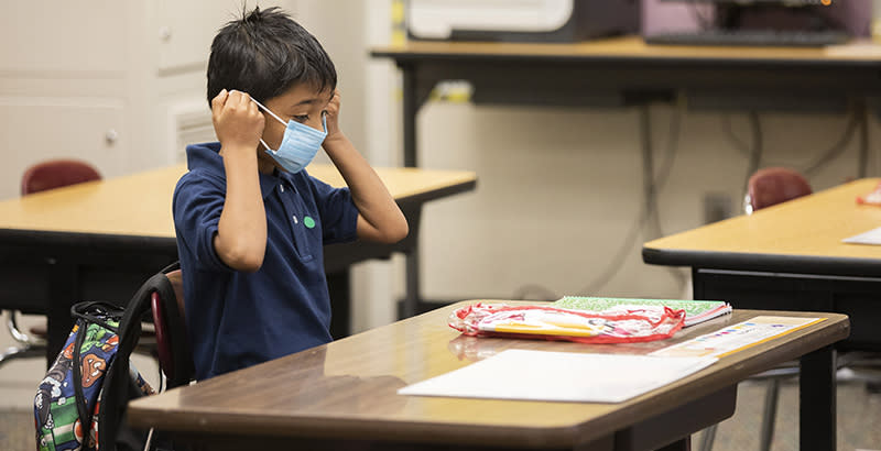 Second grader Ernesto Beltran Pastrana puts on his face mask while attending class during the first day of partial in-person instruction at Garfield Elementary School in Oakland, Calif.