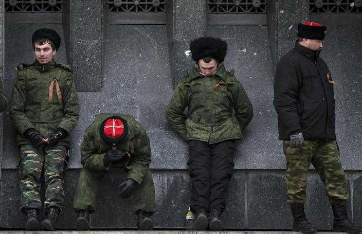 Cossacks guard the regional parliament building during the Crimean referendum in Simferopol, Ukraine, Sunday, March 16, 2014. Residents of Ukraine's Crimea region are voting in a contentious referendum on whether to split off and seek annexation by Russia. (AP Photo/Vadim Ghirda)