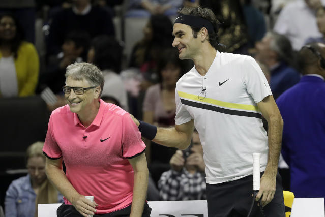 Roger Federer, of Switzerland, right, smiles after he and partner Bill Gates played in an exhibition tennis match against Jack Sock and Savannah Guthrie in San Jose, Calif., Monday, March 5, 2018. (AP Photo/Jeff Chiu)