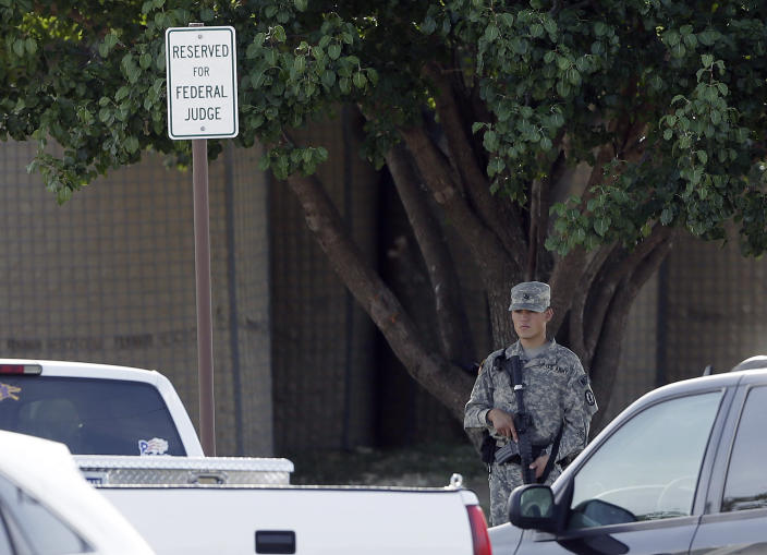 An armed guard stands in front of the fortified Lawrence William Judicial Center as the sentencing phase for Maj. Nidal Hasan continues, Wednesday, Aug. 28, 2013, in Fort Hood, Texas. Hasan was found unanimously guilty on the 13 charges of premeditated murder and is eligible for the death penalty. (AP Photo/Eric Gay)