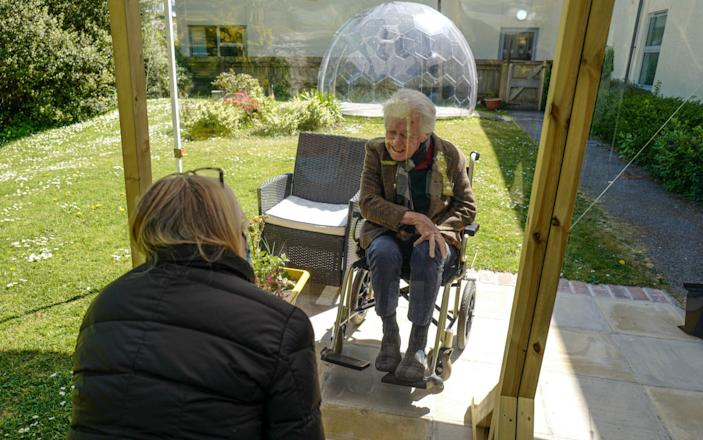 Karen Hastings visits her stepfather Gordon (aged 80), who suffers from dementia, under a temporary open-air shelter with a clear screen between them, at the Langholme Care Home - Hugh R Hastings / Getty