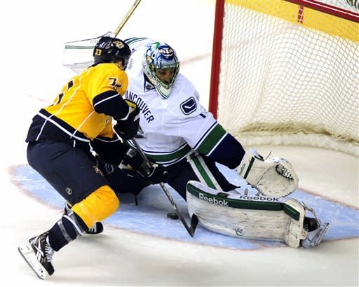 Vancouver Canucks goalie Roberto Luongo (1) makes a save against Nashville Predators center Colin Wilson (33) during a shootout of an NHL hockey game on Tuesday, Feb. 7, 2012, in Nashville, Tenn. Vancouver won 4-3. (AP Photo/Mike Strasinger)