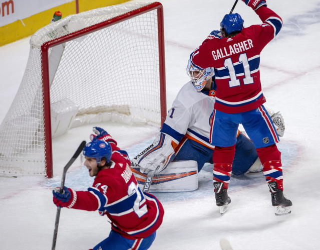 Montreal Canadiens wingers Phillip Danault (24) and Brendan Gallagher (11) celebrate after Danault scored the first goal against New York Islanders goaltender Thomas Greiss (1) during first period NHL hockey action, Tuesday, Dec. 3, 2019 in Montreal. (Ryan Remiorz/The Canadian Press via AP)