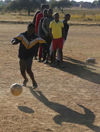 A young player controls a ball during a training session under the watchful eye of Double amputee and soccer coach, Tebogo Mofokeng, during training in Winterveldt, South Africa, Sunday, June 17, 2018. Mofokeng's legs were amputated when he was a toddler but that didn't stop him fulfilling his dream of coaching young children. (AP Photo/Denis Farrell)