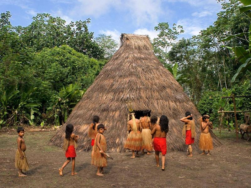 Yagua tribe next to their Maloca, a traditional house with thatched roof, in Iquitos, Amazonian, Peru. (Alamy)