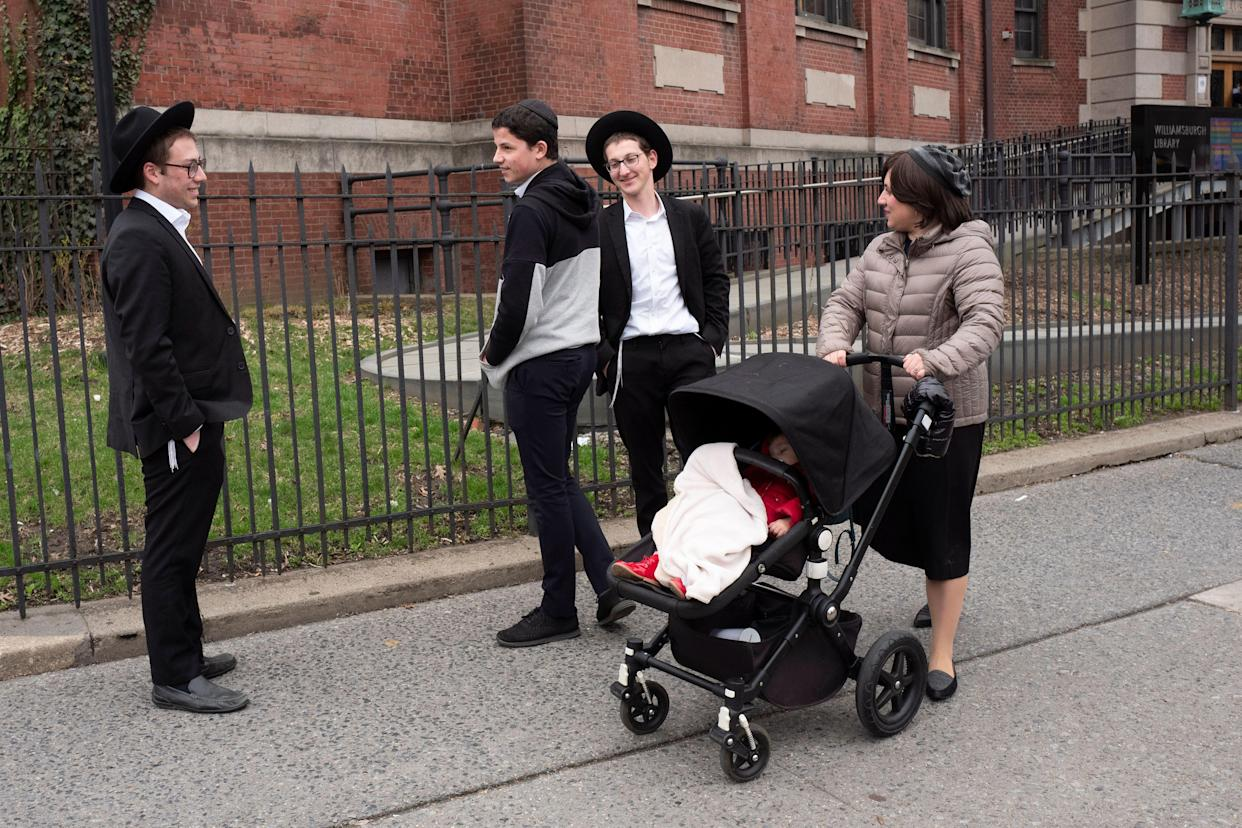 A woman, right, who identified herself as Ester, passes a group of boys, Tuesday, April 9, 2019, in the Williamsburg section of Brooklyn, New York. (AP Photo/Mark Lennihan)