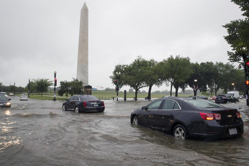Heavy rainfall flooded the intersection of 15th Street and Constitution Ave., NW stalling cars in the street, Monday, July 8, 2019, in Washington near the Washington Monument. (AP Photo/Alex Brandon)