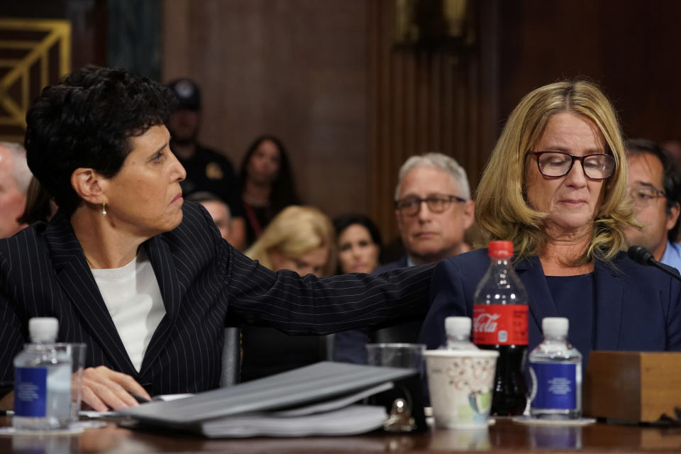 FILE - In this Thursday, Sept. 27, 2018 file photo, attorney Debra Katz reaches out to Christine Blasey Ford as she testifies before the Senate Judiciary Committee on Capitol Hill in Washington. On Wednesday, June 30, 2021, as the nation watched Bill Cosby released from prison, some worried it would have a chilling effect on survivors, who often don't come forward because they don't believe it will bring justice. And they wondered whether some of the movement's momentum, already slowed by the pandemic, would be lost amid the feeling that another powerful man had gotten away with it — albeit on a technicality. (AP Photo/Andrew Harnik, Pool, File)