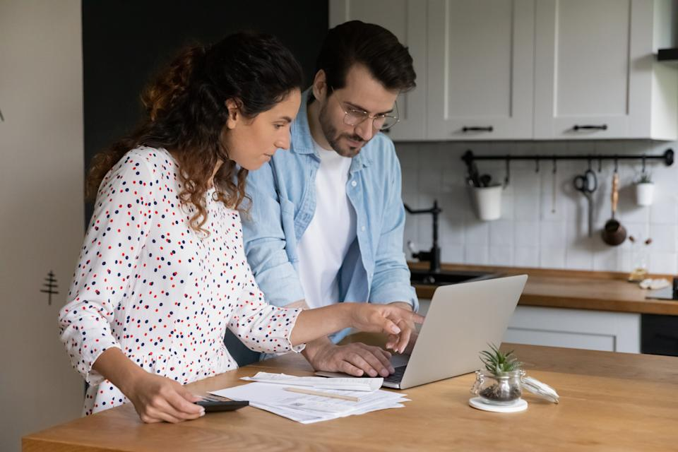 Focused man wearing glasses and woman using laptop, browsing online banking service, checking financial documents, planning budget, standing at table in kitchen, wife and husband calculating bills