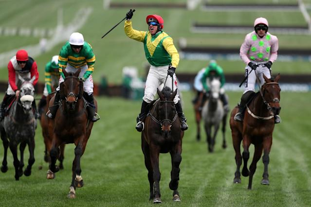 <p>Jockey Robbie Power (centre) celebrates after his winning ride on Sizing John in the Timico Cheltenham Gold Cup Chase </p>