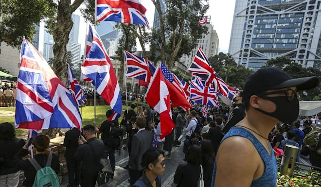 Protesters wave flags during the Remembrance Day Ceremony at The Cenotaph, Statue Square, Central. Photo: Jonathan Wong