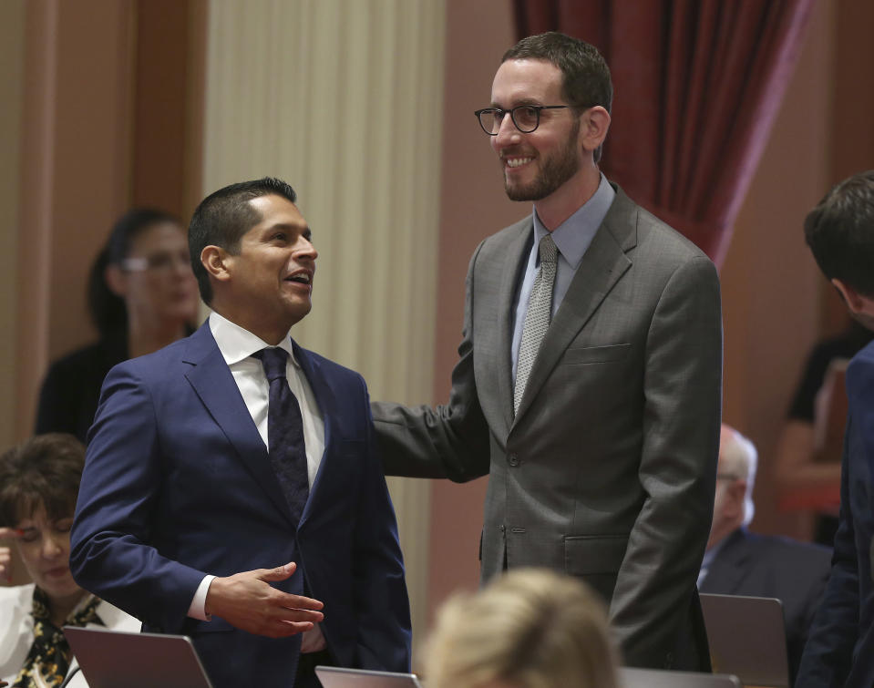 FILE - In this Aug. 31, 2018, file photo, Assemblyman Miguel Santiago, left, D-Los Angeles, left, and Sen. Scott Wiener, D-San Francisco, smile after their net neutrality bill was approved by the Senate, Friday, Aug. 31, 2018, in Sacramento, Calif. The Trump administration sued to block California's 2018 law, preventing it from taking effect for years. The Biden administration dropped that suit. The telecom industry is still fighting the law, but a judge ruled in February that California could begin enforcing it. (AP Photo/Rich Pedroncelli, File)