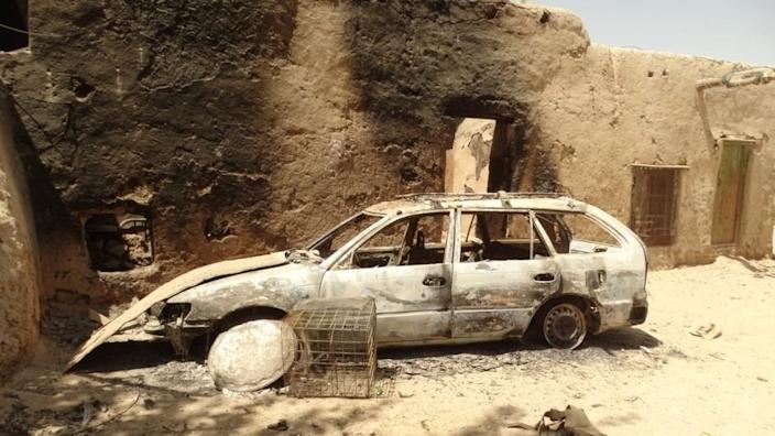 A burned out car next to a badly burned building