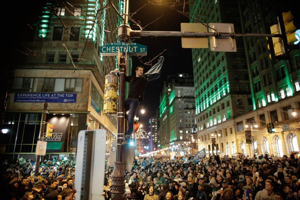 <p>A man climbs a traffic pole as Philadelphia Eagles fans celebrate victory in Super Bowl LII against the New England Patriots on Feb. 4, 2018 in Philadelphia, Pennsylvania. Photo from Eduardo Munoz Alvarez/Getty Images. </p>