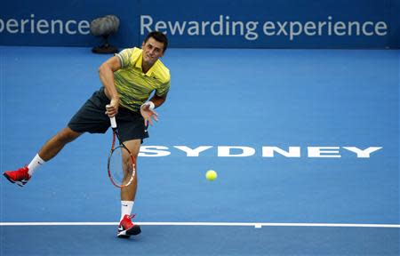 Bernard Tomic of Australia serves to Marcel Granollers of France during their first round match at the Sydney International tennis tournament January 7, 2014. REUTERS/Jason Reed
