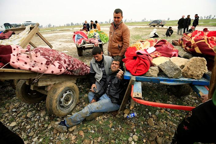 Relatives with the bodies of civilians killed in the airstrike in west Mosul. (Photo: Thaier Al-Sudani/Reuters)