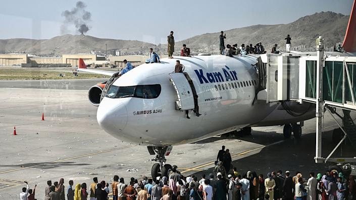 Afghan people climb atop a plane at the airport in Kabul, Afghanistan, on Monday. (Photo by Wakil Koshar/AFP via Getty Images)