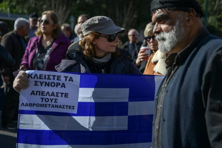 """A woman holds a Greek flag and a placard reading """"Close the borders, Deport the illegal migrants"""" during a demonstration in Athens on February 13 against the government's plans to build new migrant camps"""