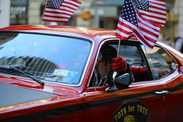 <p>A veteran drives an old Plymouth while waving a flag up Fifth Avenue during the Veterans Day parade in New York City on Nov. 11, 2017. (Photo: Gordon Donovan/Yahoo News) </p>