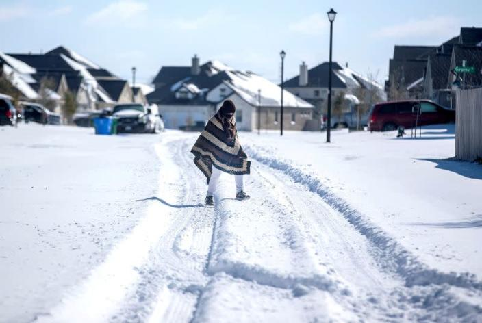 FILE PHOTO: A man walks to his friend's home in a neighbourhood without electricity as snow covers the BlackHawk neighborhood in Pflugerville