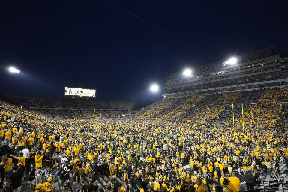 Fans storm the field after Iowa beat Penn State 23-20, in an NCAA college football game, Saturday, Oct. 9, 2021, in Iowa City, Iowa. (AP Photo/Matthew Putney)