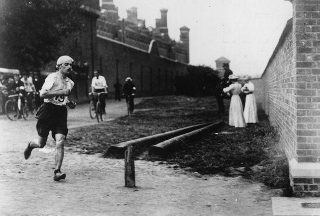 Italian runner Dorando Pietri (1885 - 1942) at Wormwood Scrubs near where he took the lead in the last mile of the Marathon event at the 1908 London Olympics, 24th July 1908. Behind him is Wormwood Scrubs prison. Despite finishing first, he was disqualified for being helped over the line after collapsing just yards from the end. The Gold Medal went to John Hayes of the USA.  (Photo by Hulton Archive/Getty Images) (Photo: Hulton Archive via Getty Images)