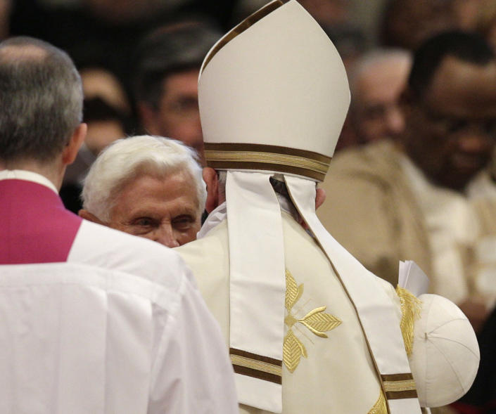 Pope Emeritus Benedict XVI is greeted by Pope Francis, right, with back to camera, as he arrives for a consistory inside the St. Peter's Basilica at the Vatican, Saturday, Feb.22, 2014. Benedict XVI has joined Pope Francis in a ceremony creating the cardinals who will elect their successor in an unprecedented blending of papacies past, present and future. (AP Photo/Alessandra Tarantino)
