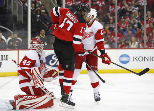 New Jersey Devils right wing Wayne Simmonds (17) leaps to allow the puck a path to the goal as Detroit Red Wings goaltender Jonathan Bernier (45) makes a save against his chest during the second period of an NHL hockey game, Thursday, Feb. 13, 2020, in Newark, N.J. (AP Photo/Kathy Willens)