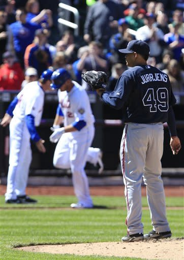 Atlanta Braves starting pitcher Jair Jurrjens (49) looks on as New York Mets' Lucas Duda celebrates with third base coach Tim Teufel during the fourth inning of a baseball game Saturday, April 7, 2012, in New York. (AP Photo/Frank Franklin II)