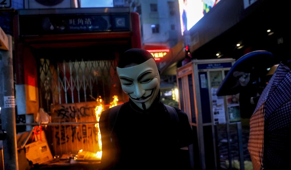 A masked anti-government protester on Sunday leaves after helping to set a fire at the entrance of an MTR station. Photo: Reuters