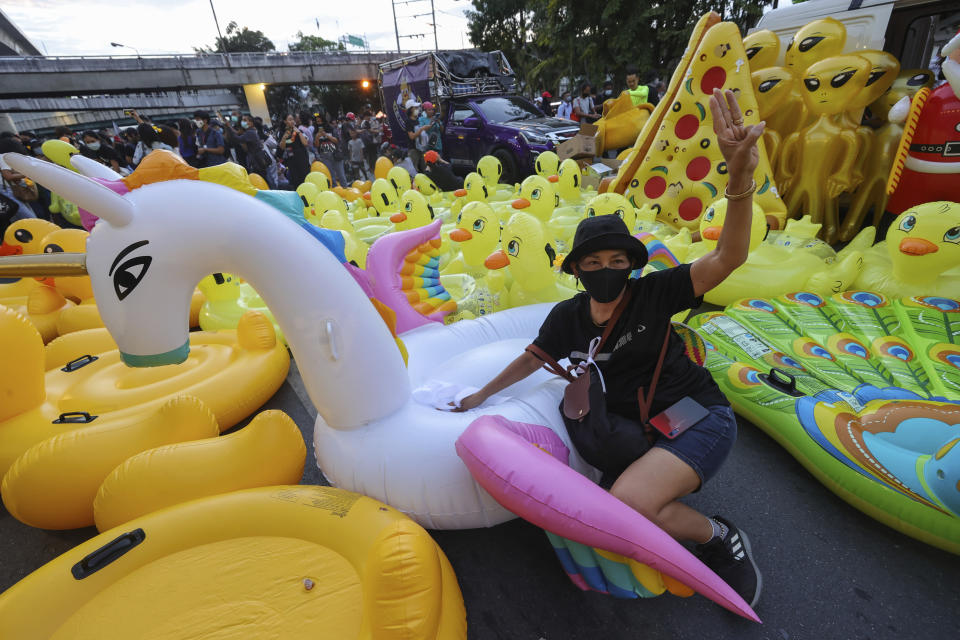 CORRECTS PHOTOGRAPHER'S NAME - A woman flashes a three-finger protest gesture while posing in front of mostly inflatable yellow ducks, which have become good-humored symbols of resistance during anti-government rallies, Friday, Nov. 27, 2020 in Bangkok, Thailand. Pro-democracy demonstrators are continuing their protests calling for the government to step down and reforms to the constitution and the monarchy, despite legal charges being filed against them and the possibility of violence from their opponents or a military crackdown. (AP Photo/Wason Wanichakorn)