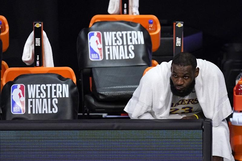 Los Angeles Lakers forward LeBron James watches play against the Denver Nuggets from the bench.