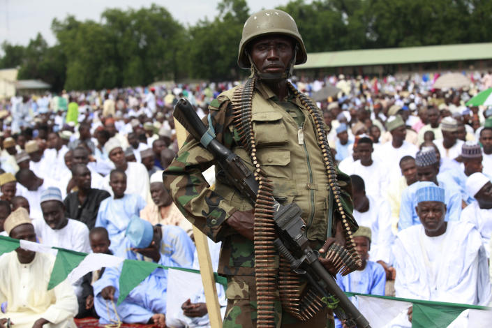 """A Nigeria soldier provides security during Eid al-Fitr prayers at Ramat square in Maiduguri, northeastern Nigeria, Thursday, Aug. 8, 2013. Nigerians in the birthplace of an Islamic uprising gripping the northeast Thursday celebrated the Muslim holy day of Eid al-Fitr with devout prayers and a joyful show of adulation for their king that attracted more than 10,000 people. It was the first durbar in three years in the city of Maiduguri and the joy that it could take place - albeit amid massive security - was heard in the cries of ululating women, screams of delight from children and men chanting """"Long live the king!"""" (AP Photo/Sunday Alamba)"""