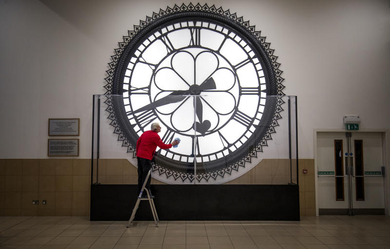 Dougie Cook, from the housekeeping team, cleans the St Enoch Clock in the Antonine Centre in Cumbernauld. The historic clock originally hung from the roof of the old St Enoch railway station in Glasgow and was made famous when it featured prominently in the 1981 film 'Gregory's Girl'. (Photo by Jane Barlow/PA Images via Getty Images)