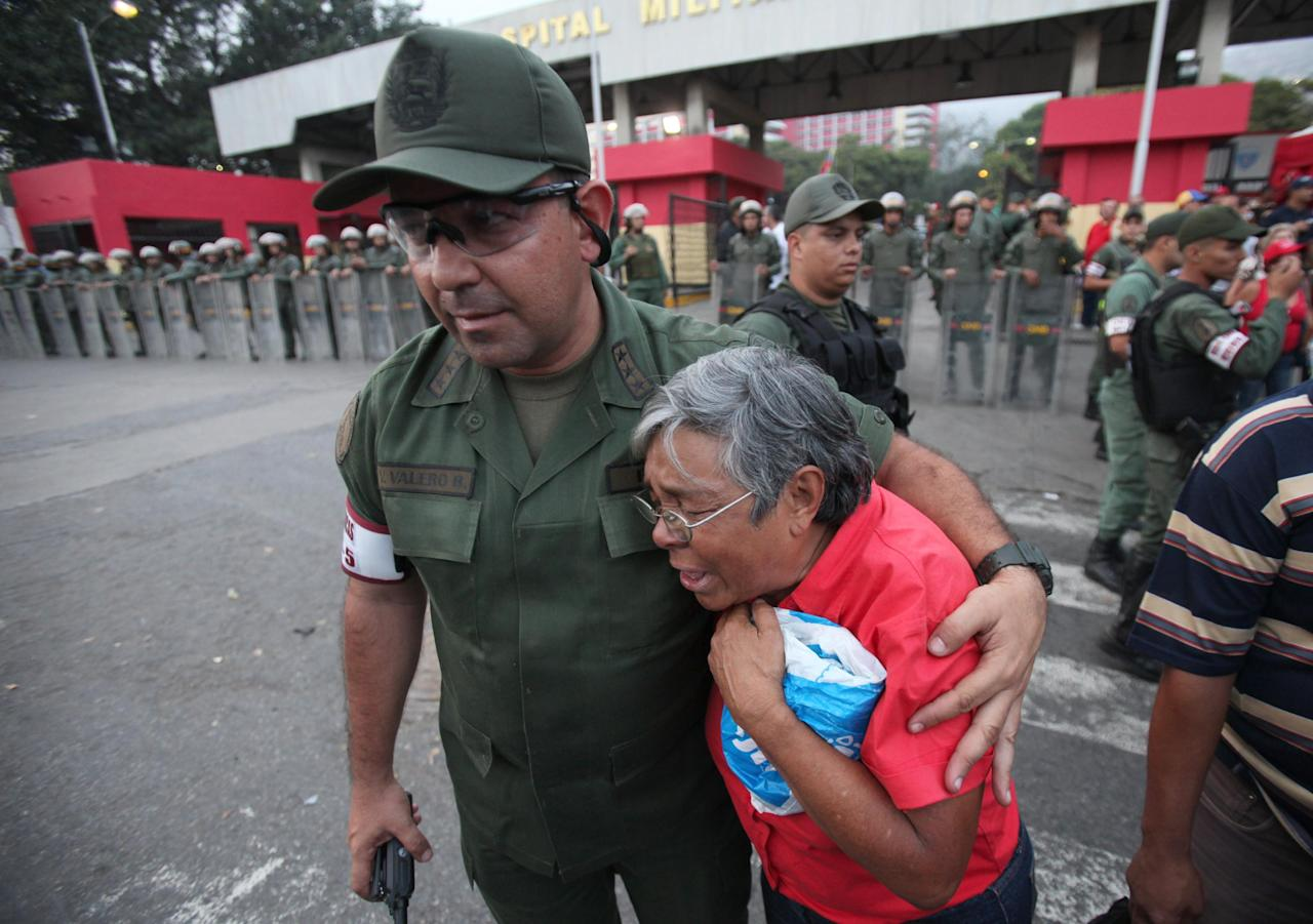 An army officer comforts a upporter of President Hugo Chavez outside the military hospital in Caracas, Venezuela, Tuesday, March 5, 2013. Venezuela's Vice President Nicolas Maduro announced that Chavez died on Tuesday at age 58 after a nearly two-year bout with cancer. During more than 14 years in office, Chavez routinely challenged the status quo at home and internationally. He polarized Venezuelans with his confrontational and domineering style, yet was also a masterful communicator and strategist who tapped into Venezuelan nationalism to win broad support, particularly among the poor.(AP Photo/Fernando Llano)