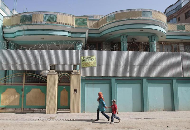 In this Monday, July 16, 2012 photo Afghans walk past by a house for rent in Kabul, Afghanistan. Donor nations have pledged to keep bankrolling the Afghan security forces and send more development money, but none of this has done much to raise the hopes of many Afghans who remain in deep despair about the future of their nation after international troops leave. (AP Photo/Musadeq Sadeq)