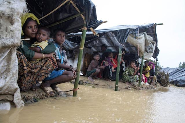 <p>Refugees shelter from a downpour as the monsoon rains create massive challenges for the displaced Rohingya on September 17 in Kutupalong, Cox's Bazar, Bangladesh. The family of four is still waiting for a tent. (Photograph by Paula Bronstein/Getty Images) </p>