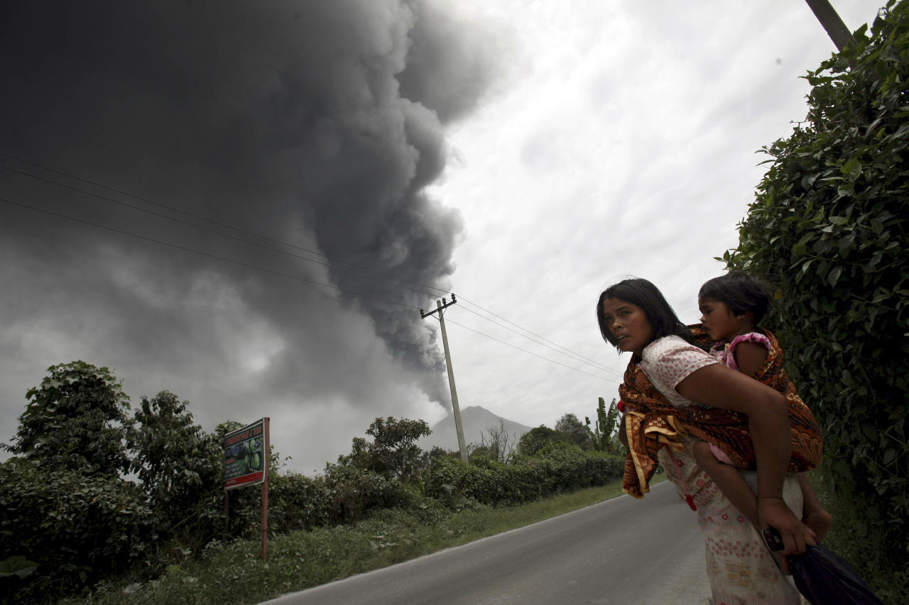 AP10ThingsToSee - A woman and her daughter flee their home as Mount Sinabung erupts in Karo, North Sumatra, Indonesia, Tuesday, Sept. 17, 2013. Thousands of people were evacuated from their villages following the eruption of the volcano Sunday after being dormant for three years, sending thick ash into the sky with small rocks pelting neighboring villages. (AP Photo/Binsar Bakkara, File)