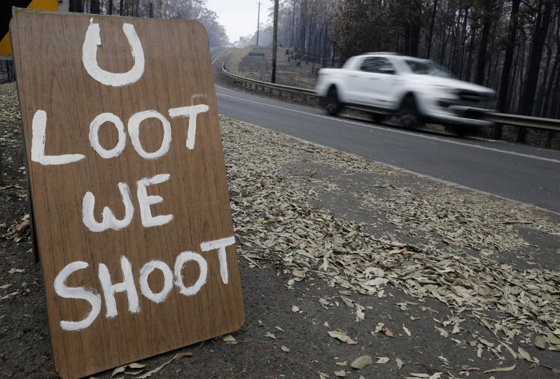 A sign discourages looters near Conjola Park. Source: AAP/Rick Rycroft