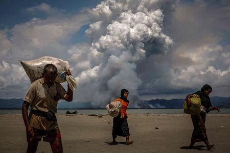 Smoke is seen on the Myanmar border as Rohingya refugees walk on the shore after crossing the Bangladesh-Myanmar border by boat through the Bay of Bengal, in Shah Porir Dwip, Bangladesh September 11, 2017. REUTERS/Danish Siddiqui