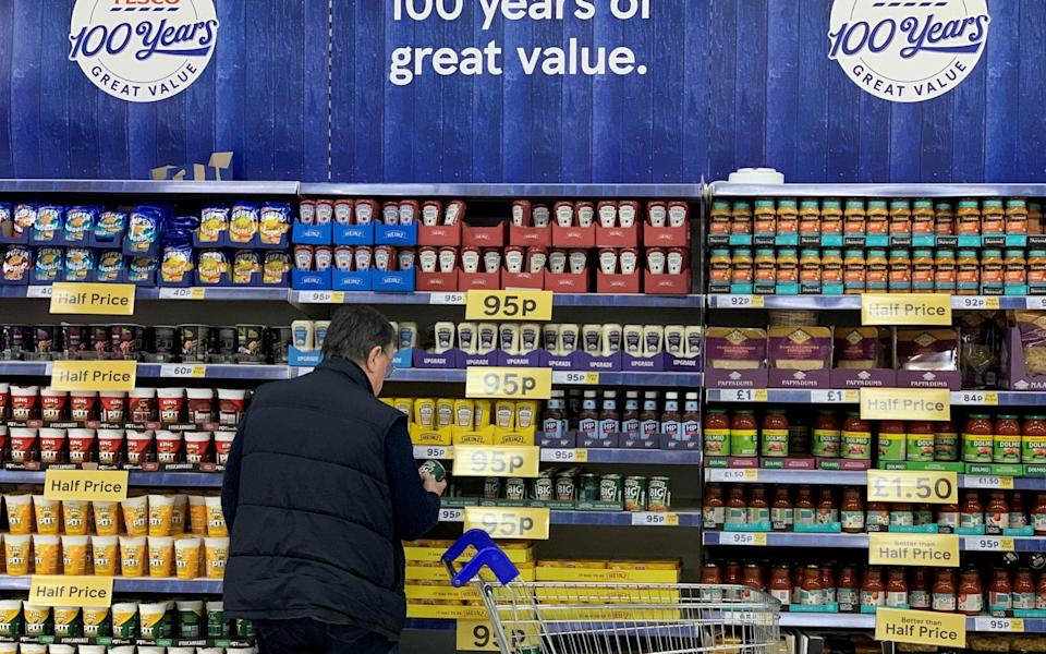 A man looks at products on a shelf inside a Tesco Extra superstore near Manchester - Phil Noble/Reuters