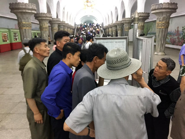 <p>Commuters read the news of North Korean leader Kim Jong Un'€™s arrival in Singapore on Monday, ahead of his summit with President Trump. (Photo: Eric Talmadge/AP) </p>